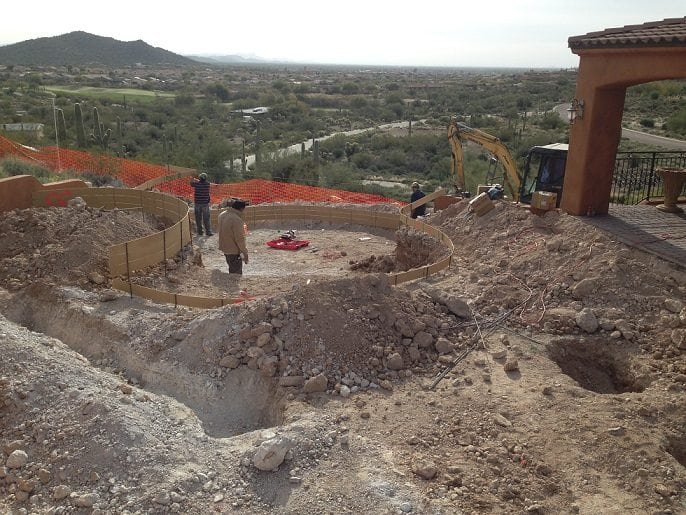 Close up view in San Antonio, Texas of men working on the excavation process for a family who is building a swimming pool.