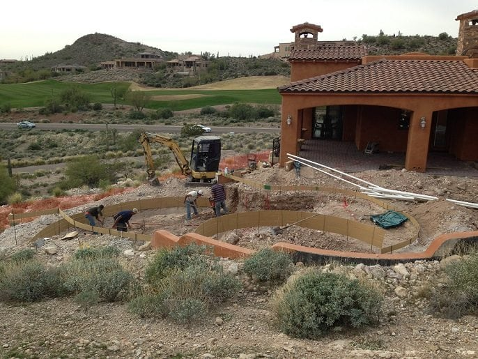 Zoomed out view of men working to build a swimming pool in San Antonio, Texas. The homeowners have decided to build a swimming pool with help from pool builders at BYOP.