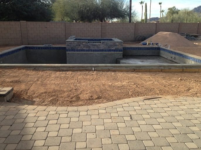 A view of an extravagant new swimming pool and tile patio surface that has been built with the help of BYOP.