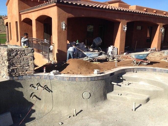 Men working on building a pool patio with tile surrounding the new swimming pool that has been built by a family in Houston, Texas.