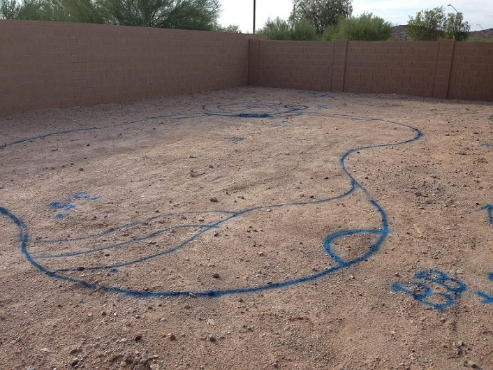 A view of a blue outline on a family's backyard in San Antonio, Texas. The outline shows a swimming pool design in their backyard. The next step is for the swimming pool excavation process with BYOP.