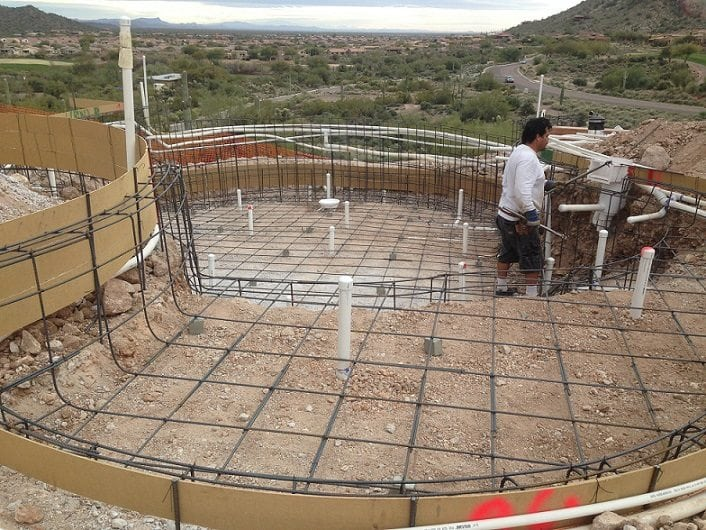 Close up of a man working on building a swimming pool in Mesa, Arizona. The man is working to install the pool rebar and the electrical system.