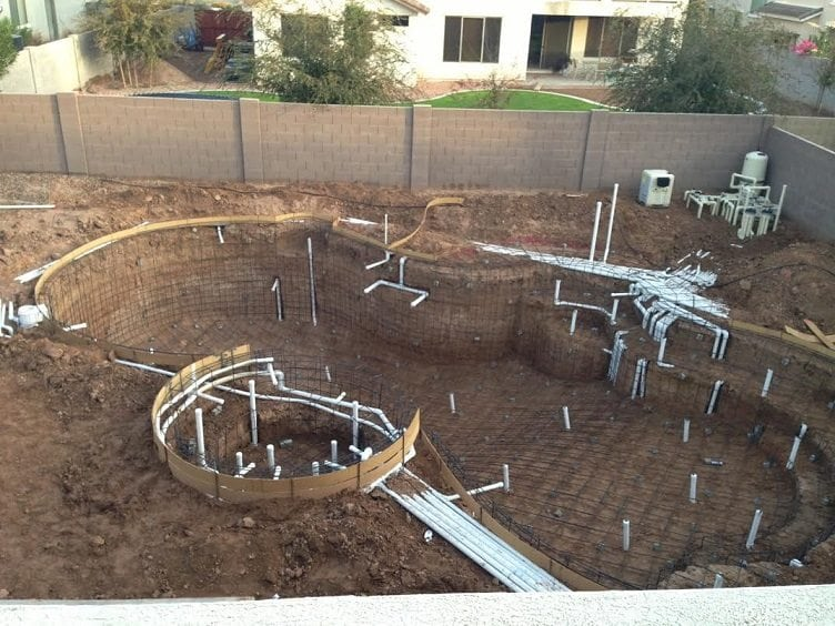 View looking down on a swimming pool that is being built in Mesa, Arizona. You can see that the pool rebar and electrical system have been added.