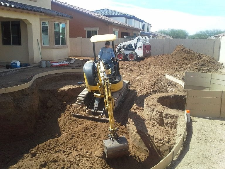 Up close view of a man working on a bulldozer for a family in Austin, Texas who is building their own pool. You can see the swimming pool design.