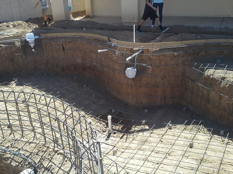 Close up view showing men working to build a swimming pool for a family in Mesa, Arizona. You are able to see that the pool rebar has been installed in this pool.