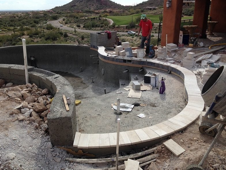 Construction underway for a pool patio surrounding a new swimming pool for a family in Phoenix, Arizona.