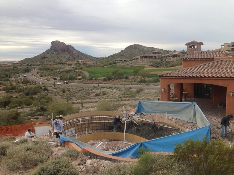Shotcrete process being performed. Shotcrete forms a strong and consistent coating for your pool.