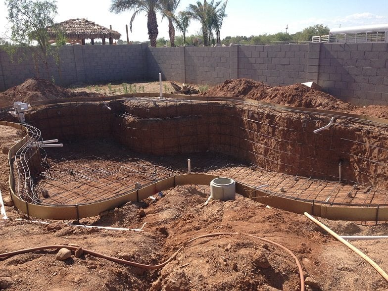 Side view of a swimming pool being built in Austin, Texas that has been finished with swimming pool rebar and an electrical system.