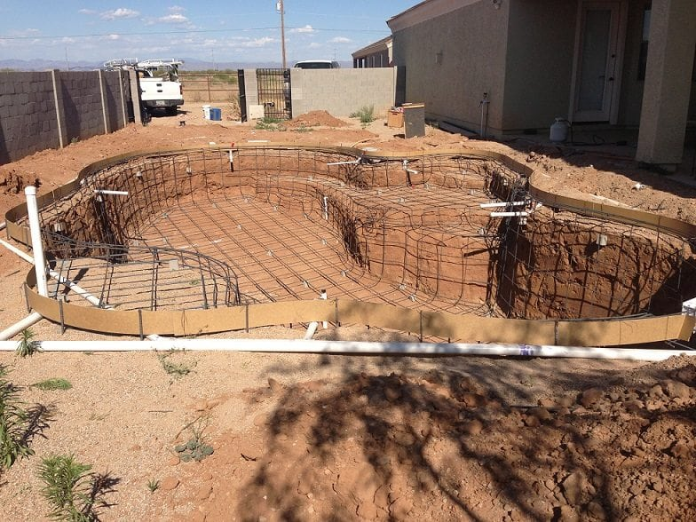 A swimming pool that is being built in Mesa, Arizona that has been equipped with pool rebar and an electrical system.