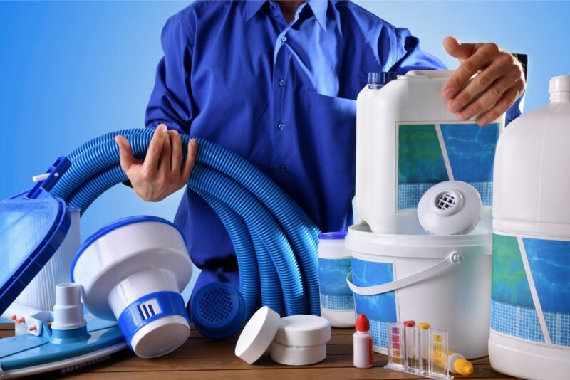 Man in blue button down shirt showing cleaning supplies for a swimming pool.