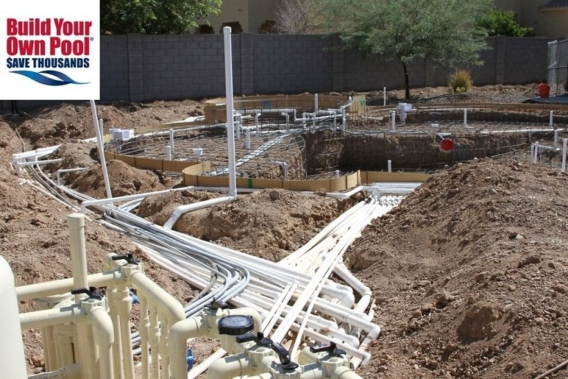 Close up view of a swimming pool being built in Phoenix, Arizona. You can see that the pool plumbing process has begun. You can see all of the pool pipes that have been installed.