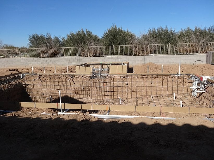 A side view of a swimming pool that has had pool steel and the electrical system installed.