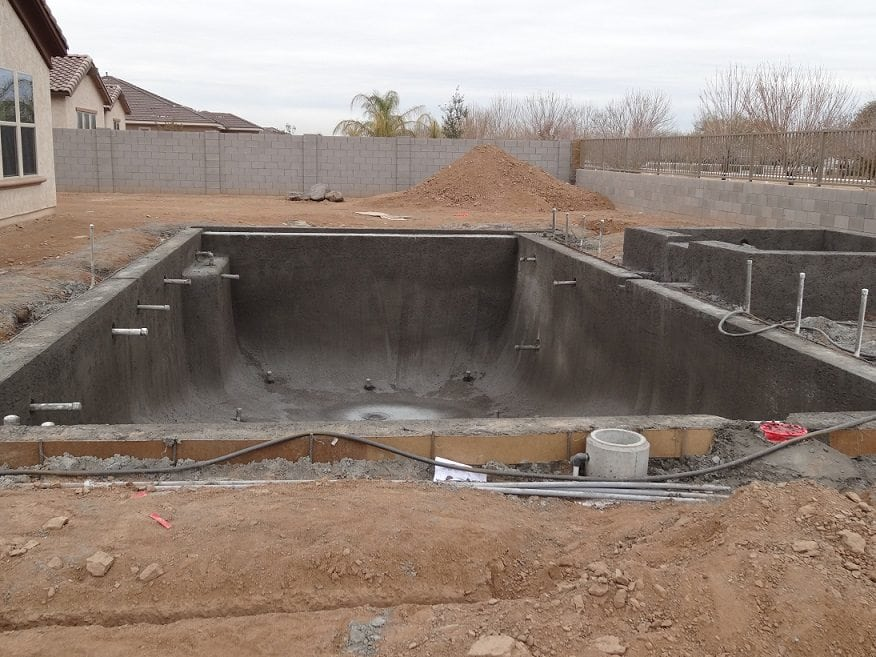Shotcrete - the builders put the mixed, wet concrete in equipment hopper and compressed air shoots the material to/through the nozzle.