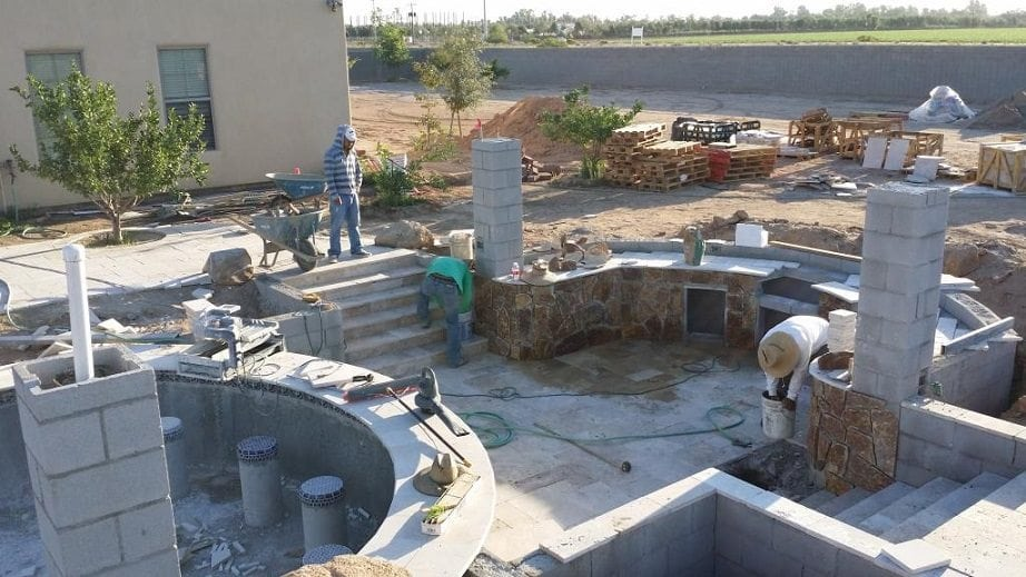 Men hard at work on a pool patio for a family in Phoenix, Arizona.