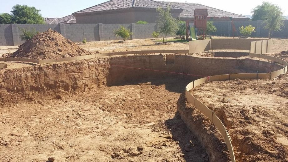 Zoomed in view of a swimming pool that is being built in a backyard. The pool excavation process has begun. You can see the swimming pool that has been designed by BYOP.