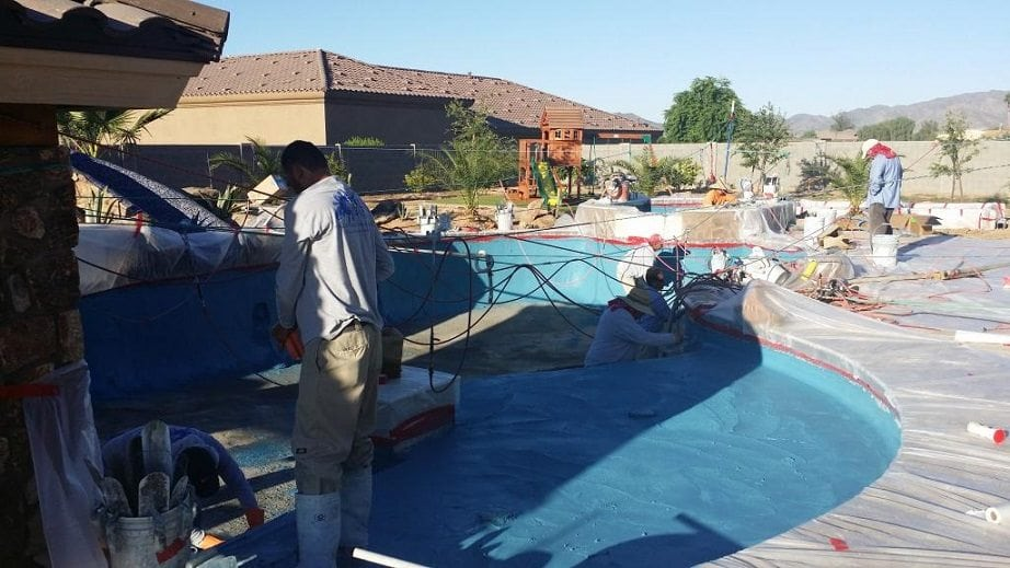 Men finishing up an interior finish for a swimming pool being built in Texas.