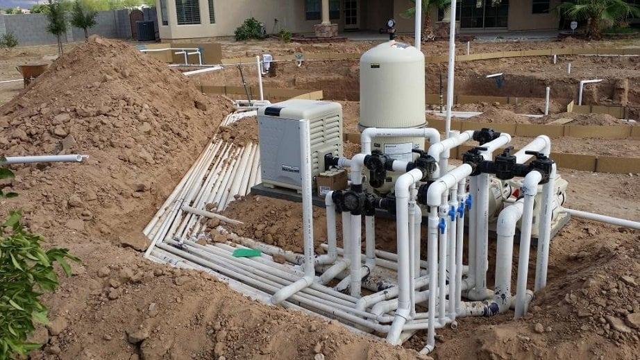 A close up view of a swimming pool plumbing system for a pool that is being built in a backyard.