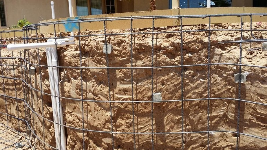 Close up view of rebar on the side of a swimming pool that is being built.