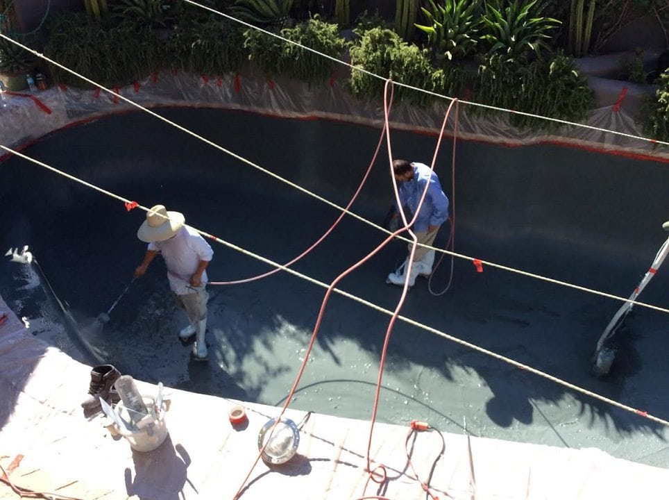Two men working on a pebble pool surface. The swimming pool has been built by a family in Mesa, Arizona with the help of BYOP.