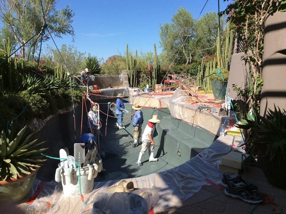 A view of five men working on a pebble finish of a swimming pool that is being built by a family in Mesa, Arizona.